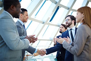 business leaders shaking hands for middle market business deal