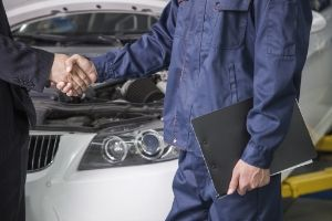 auto body shop owner and buyer shake hands
