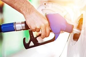 man pumping fuel into his car gas tank